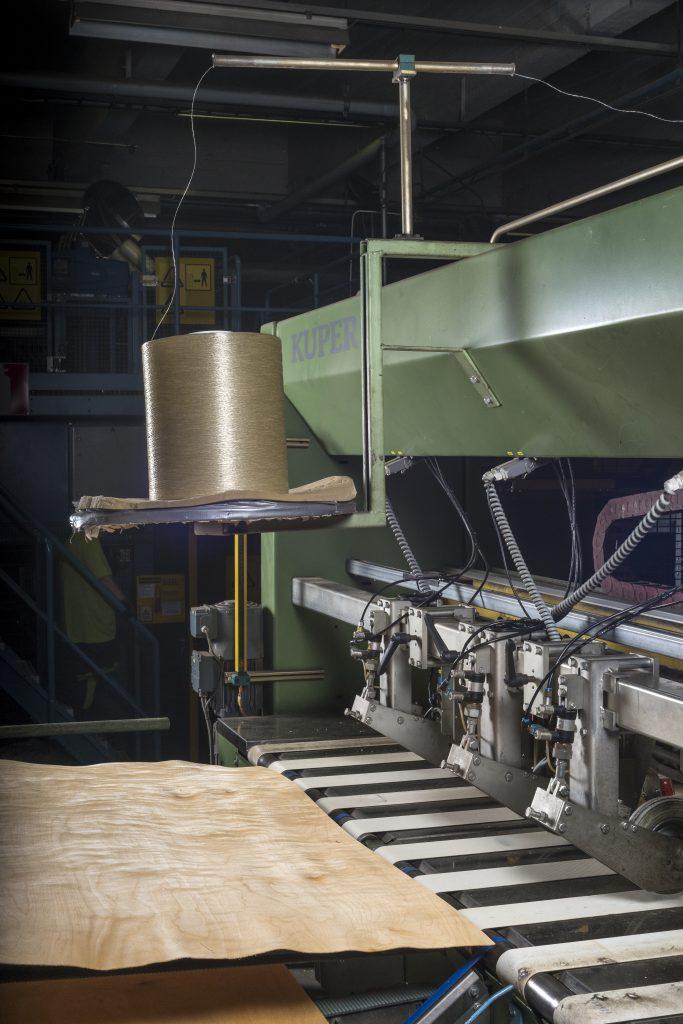 A sheet of veneer being fed into a veneer composing machine.