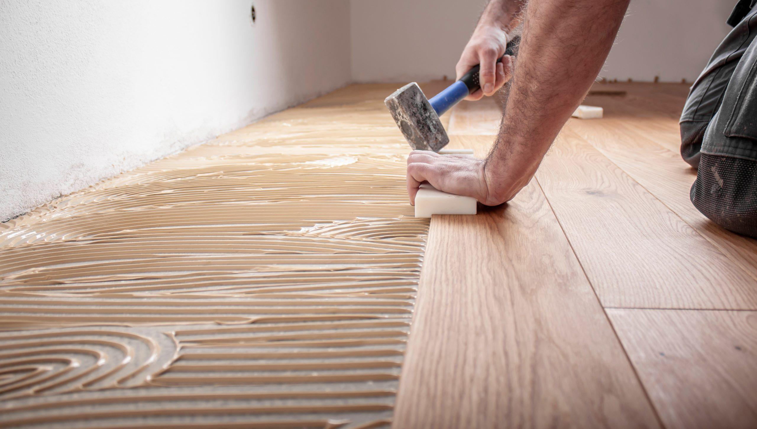 A worker laying wood flooring, ensuring the edges adhere together.
